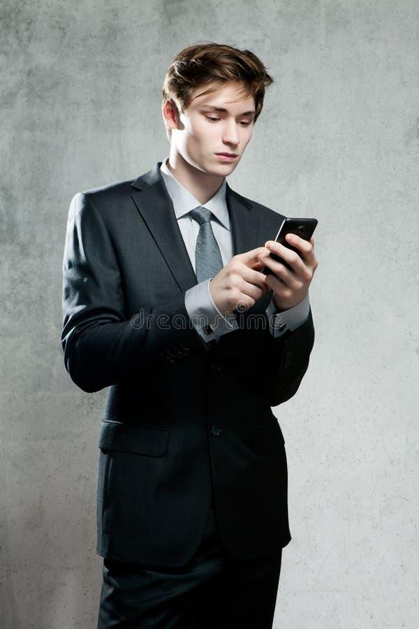 Homem de negócios novo que usa um telefone celular foto de stock royalty free