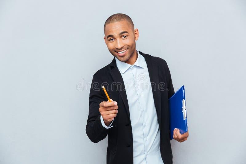 Homem de negócios novo seguro alegre que guarda a prancheta fotografia de stock royalty free