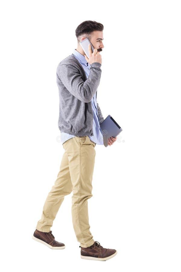 Homem de negócios novo seguro com a tabuleta no telefone, na caminhada e no olhar afastado foto de stock royalty free