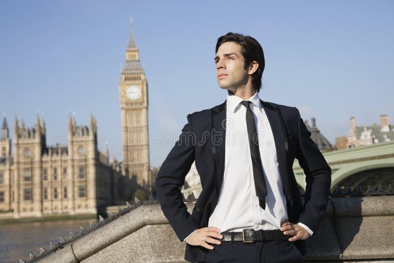 Homem de negócios novo seguro que está contra a torre de pulso de disparo de Big Ben, Londres, Reino Unido imagens de stock royalty free
