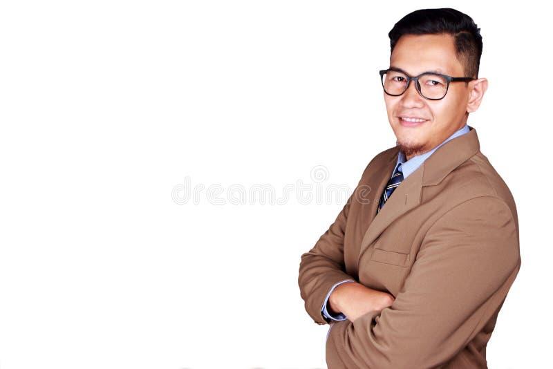 Homem de negócios novo Smiling na câmera, braço cruzado imagem de stock royalty free
