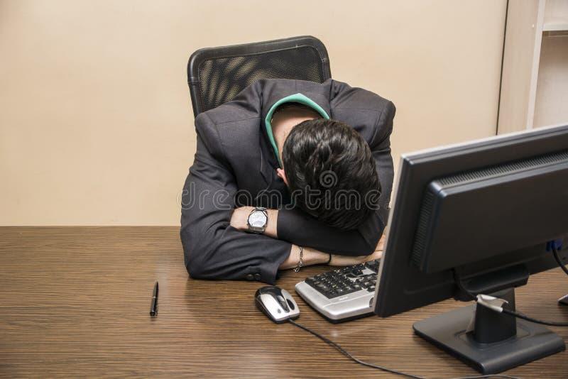 Homem de negócios novo sobrecarregado, cansado que dorme no escritório fotografia de stock