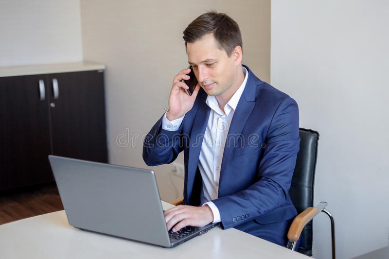 Homem de negócios novo de sorriso que senta-se atrás de sua mesa com portátil e que fala no telefone celular no escritório fotos de stock royalty free
