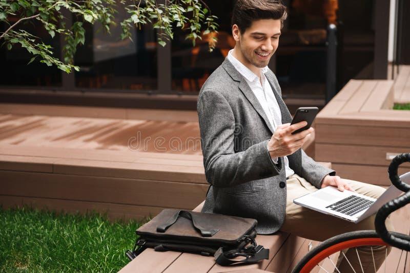 Homem de negócios novo de sorriso que usa o telefone celular fotografia de stock royalty free