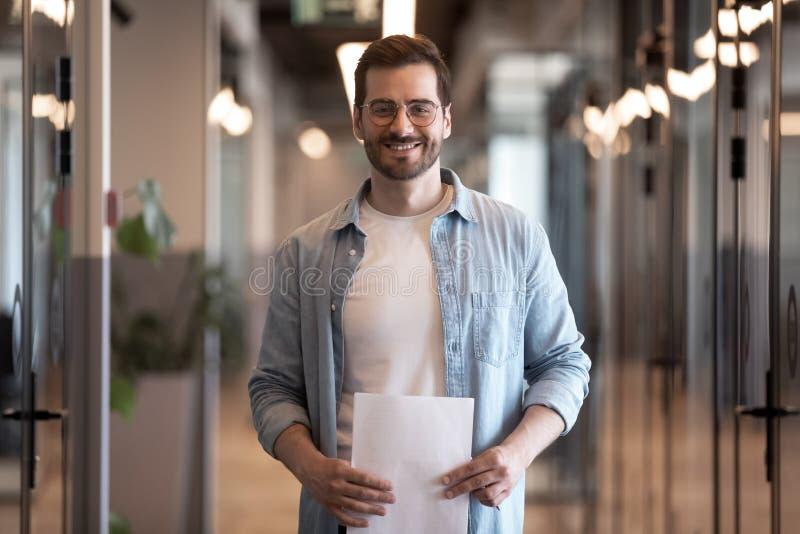 Homem de negócios novo de sorriso seguro que olha a câmera no corredor do escritório imagens de stock