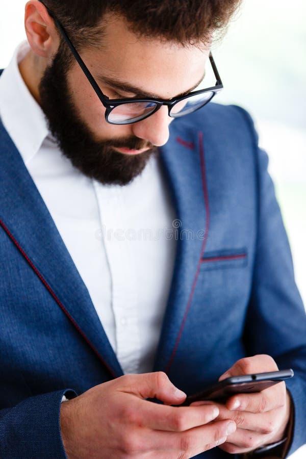 Homem de negócios novo Using Mobile Phone no local de trabalho imagens de stock royalty free
