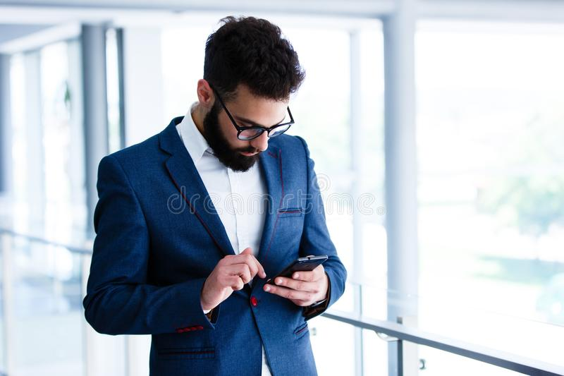 Homem de negócios novo Using Mobile Phone no local de trabalho fotos de stock