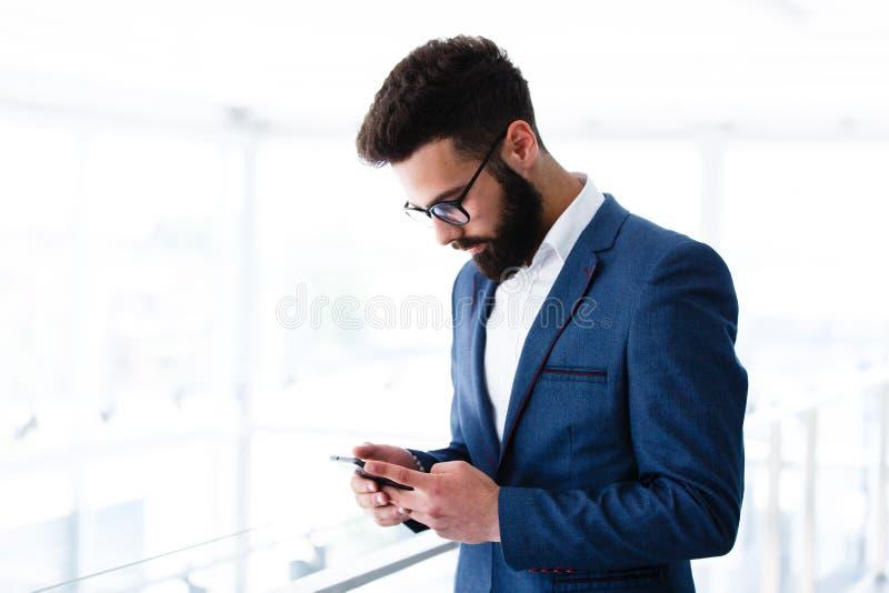 Homem de negócios novo Using Mobile Phone no local de trabalho fotografia de stock
