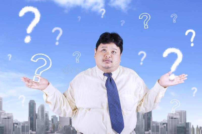 Homem de negócios obeso com pontos de interrogação imagem de stock