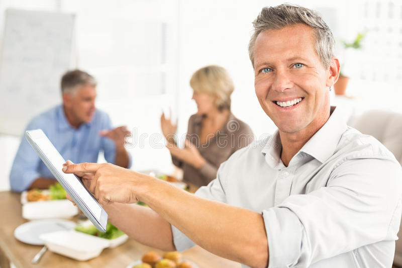 Homem de negócios ocasional de sorriso que usa a tabuleta no almoço foto de stock royalty free