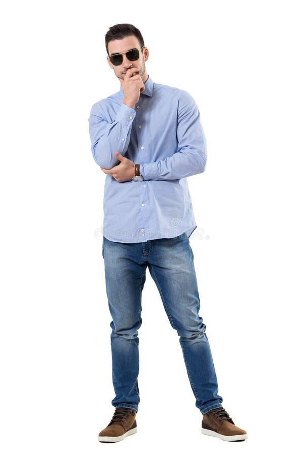 Homem de negócios ocasional esperto novo que pensa com mãos em óculos de sol vestindo do queixo imagem de stock