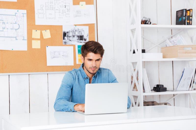 Homem de negócios ocasional farpado considerável pensativo que senta-se com portátil imagens de stock