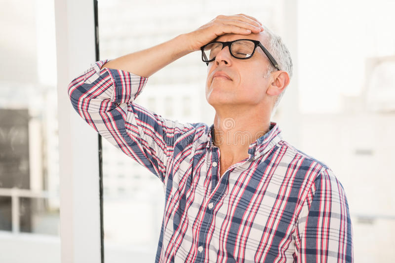 Homem de negócios ocasional incomodado que inclina-se contra a janela imagens de stock royalty free
