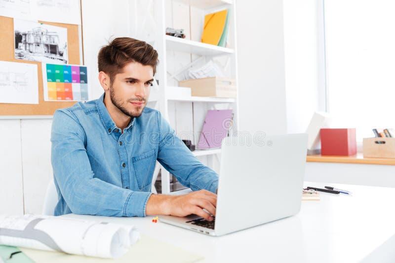 Homem de negócios ocasional novo considerável que trabalha com o portátil no escritório imagem de stock royalty free