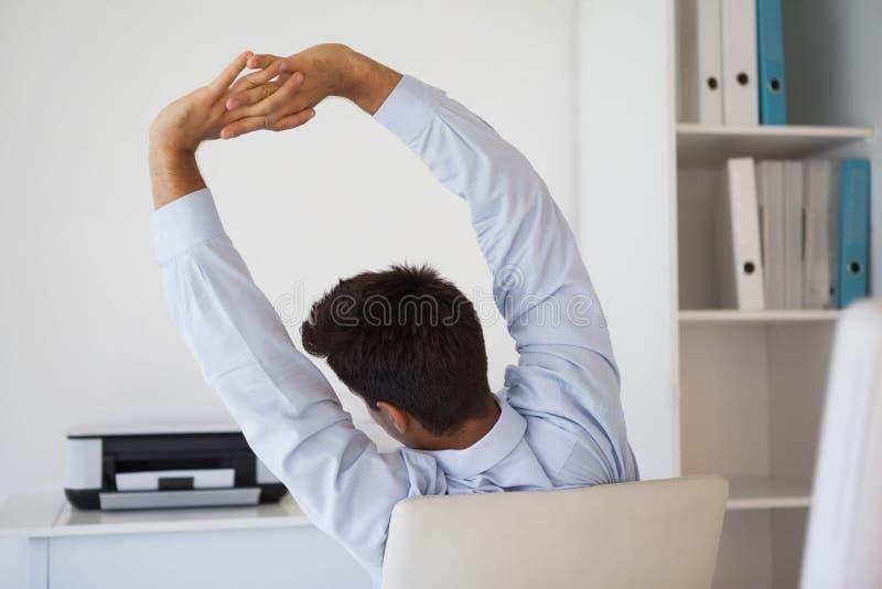 Homem de negócios ocasional que estica na cadeira de giro imagens de stock royalty free