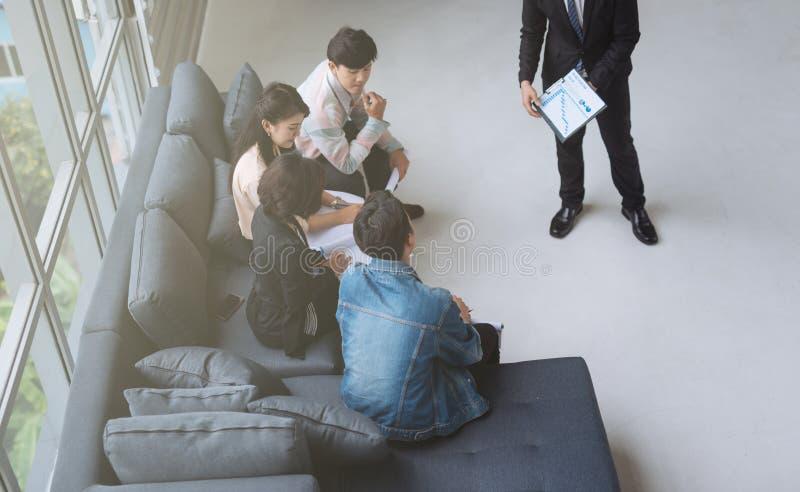 Homem de negócios ocasional que tem a reunião de negócios com seu pessoal Mostrando a apresenta??o imagem de stock royalty free