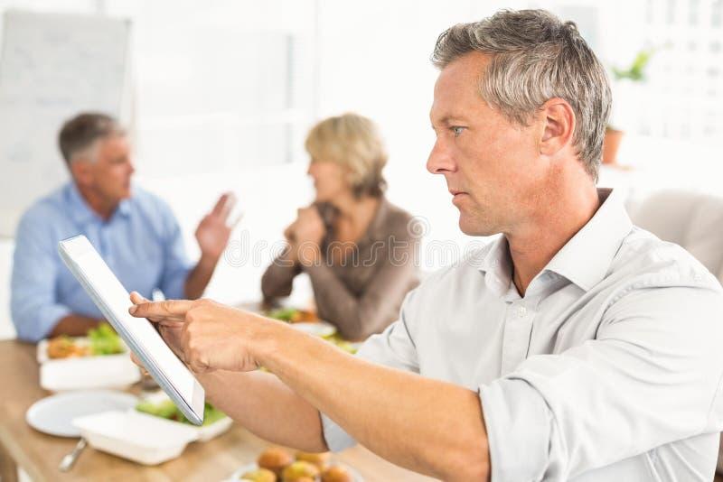 Homem de negócios ocasional que usa a tabuleta no almoço fotografia de stock royalty free