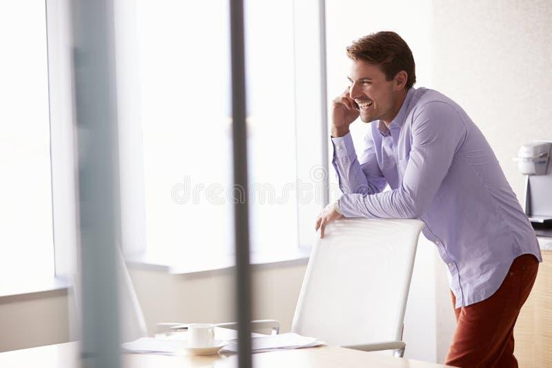 Homem de negócios ocasionalmente vestido Using Mobile Phone no escritório imagem de stock