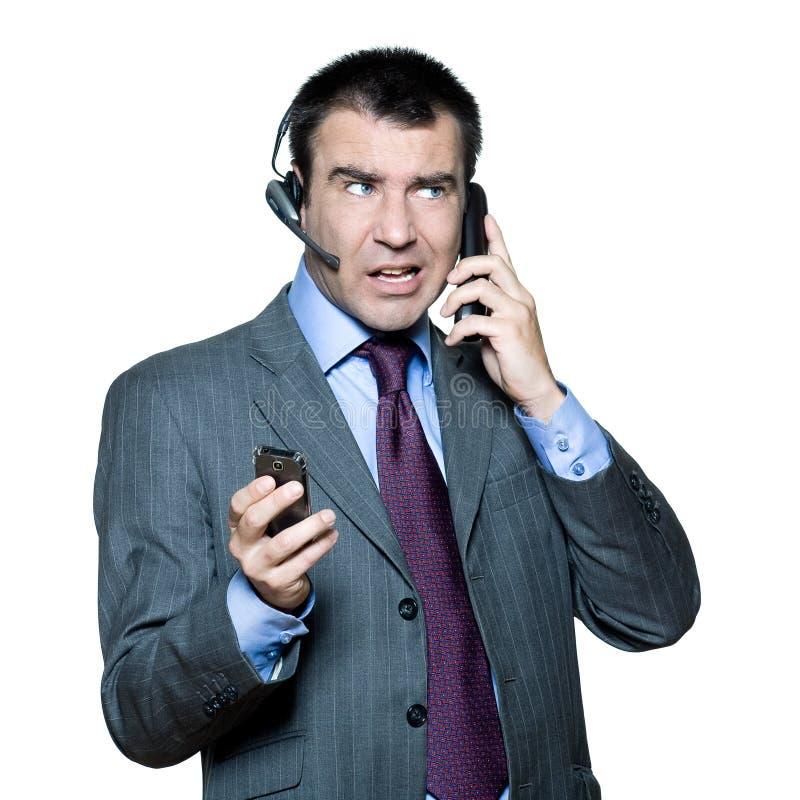 Homem de negócios ocupado com telefone múltiplo foto de stock royalty free