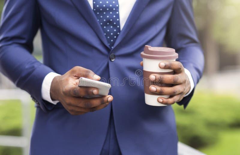 Homem de negócios ocupado que usa o smartphone e bebendo o café para viagem fora foto de stock royalty free