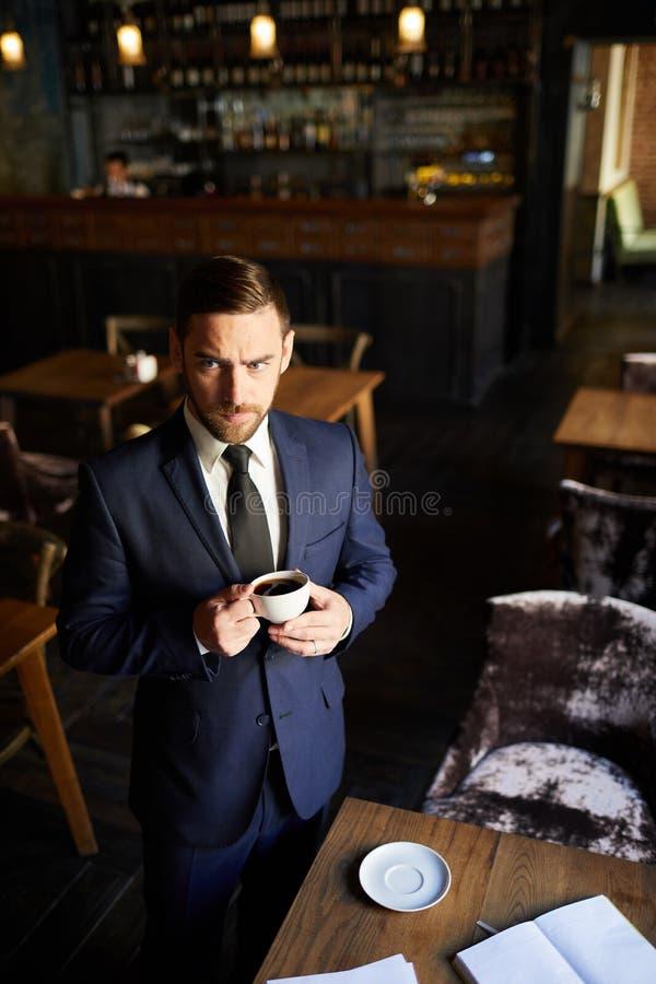 Homem de negócios olhando de sobrancelhas franzidas que está na tabela e no café bebendo imagem de stock royalty free