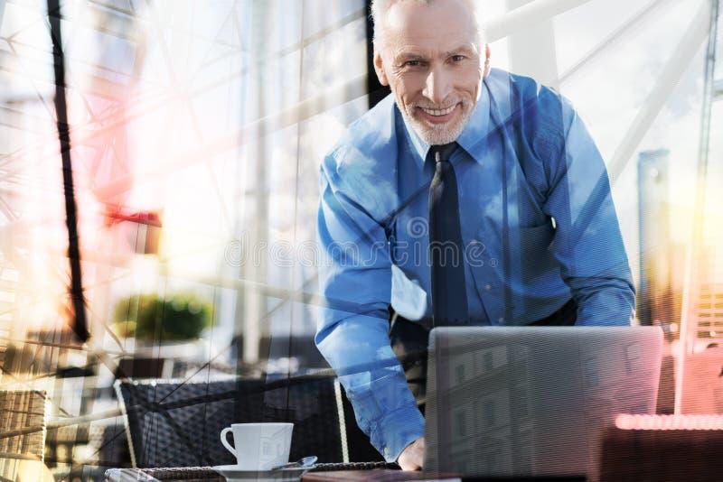 Homem de negócios otimista que está perto do portátil e que sorri alegremente fotos de stock royalty free