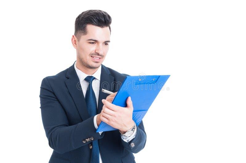 Homem de negócios ou banqueiro feliz considerável que tomam notas na prancheta imagem de stock royalty free