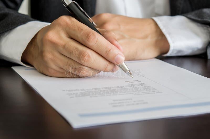 Homem de negócios ou candidato a emprego que assinam no formulário do resumo imagem de stock royalty free