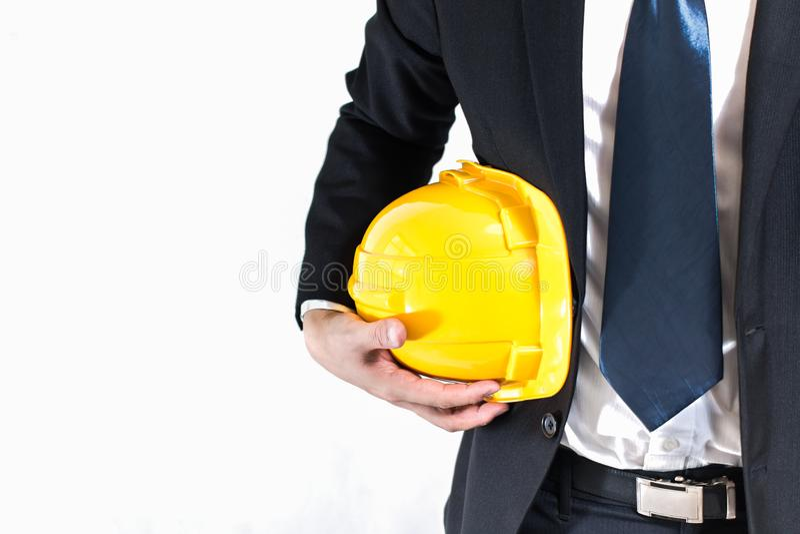 Homem de negócios ou coordenador que guardam o capacete amarelo foto de stock