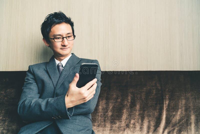 Homem de negócios ou empresário asiático que sorriem no smartphone no escritório ou na sala de conferências Conceito de uma comun fotografia de stock royalty free
