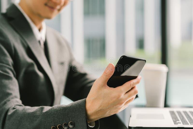 Homem de negócios ou empresário asiático que usa o smartphone e o portátil, trabalhando no escritório moderno Conceito de uma com foto de stock royalty free