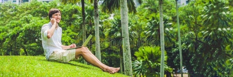 Homem de negócios ou estudante do homem da BANDEIRA no vestido ocasional usando o portátil em um parque tropical no fundo dos arr fotos de stock royalty free