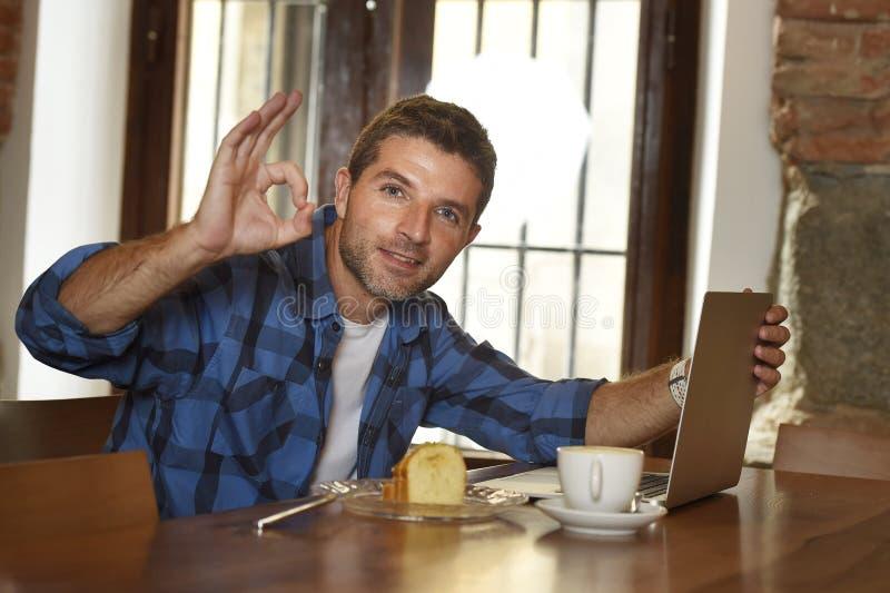 Homem de negócios ou estudante que trabalham com o laptop na cafetaria que come o café da manhã foto de stock royalty free