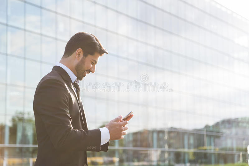 Homem de negócios ou trabalhador bem sucedido que estão no terno com telefone celular foto de stock