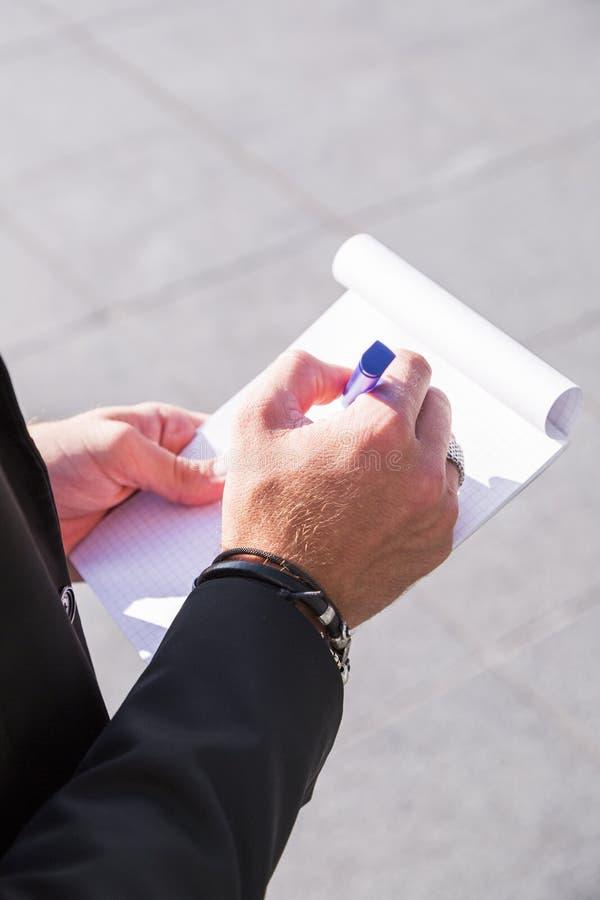 Homem de negócios ou trabalhador masculino na escrita preta do terno no caderno imagens de stock royalty free