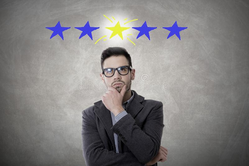 Homem de negócios pensativo com estrelas imagem de stock