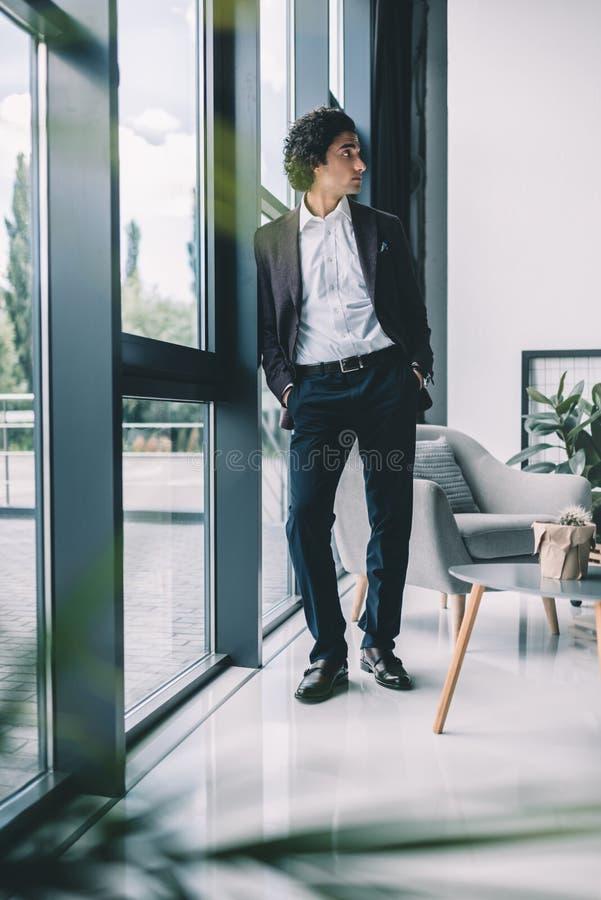 homem de negócios pensativo com mãos em uns bolsos que estão na janela foto de stock royalty free