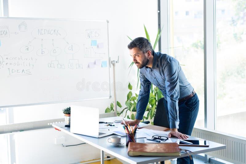 Homem de negócios pensativo com o portátil em seu escritório imagens de stock