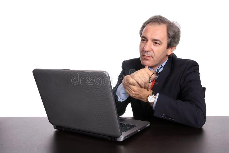 Homem de negócios pensativo com o portátil em sua mesa fotos de stock royalty free