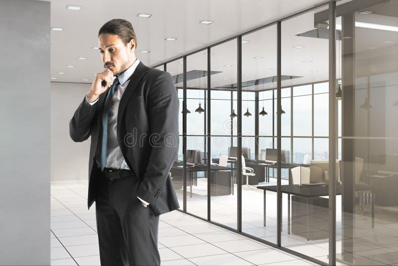 Homem de negócios pensativo no escritório contemporâneo imagem de stock