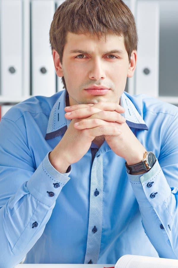 Homem de negócios pensativo novo que senta-se no local de trabalho do escritório que olha em linha reta à câmera imagens de stock