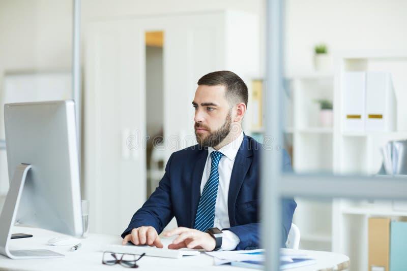 Homem de negócios pensativo que analisa dados estatísticos imagem de stock