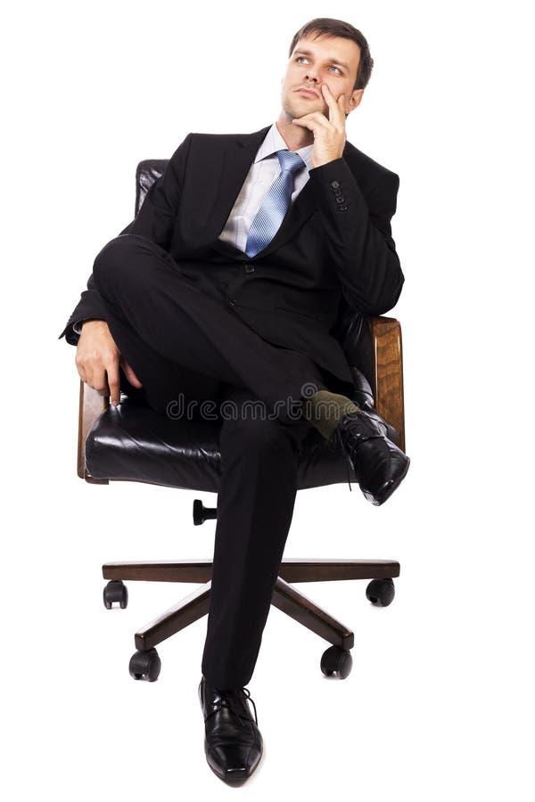 Homem de negócios pensativo que senta-se em uma poltrona e que olha acima imagem de stock royalty free