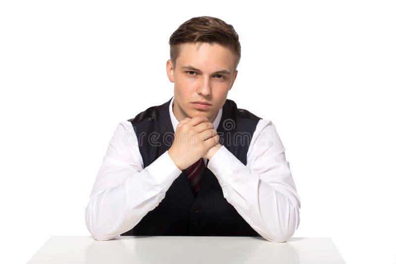 Homem de negócios pensativo que senta-se na tabela isolada no fundo branco imagem de stock royalty free