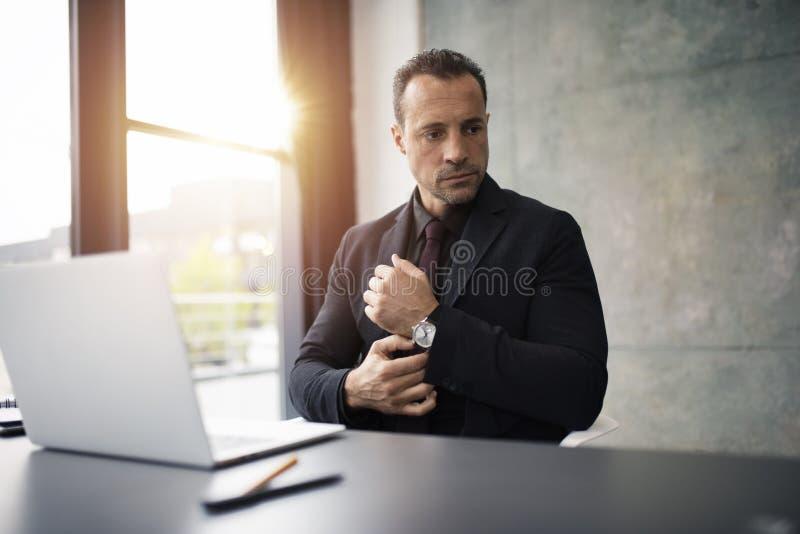 Homem de negócios pensativo que trabalha com um portátil no escritório fotos de stock royalty free