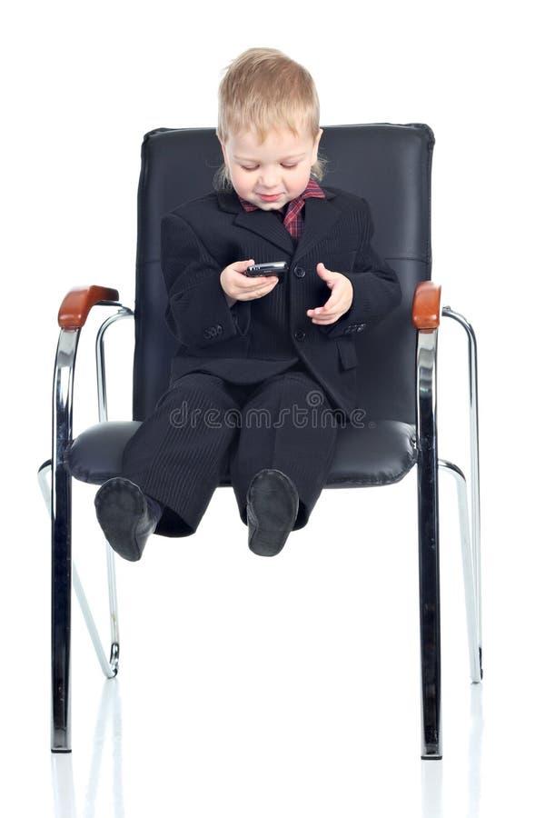 Homem de negócios pequeno com um telefone imagem de stock