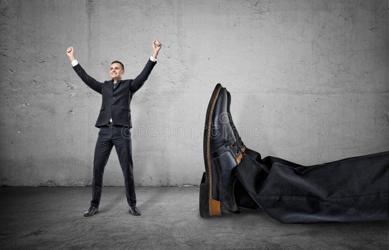 Homem de negócios pequeno que está com seus braços acima do pé gigante próximo de um outro homem imagem de stock