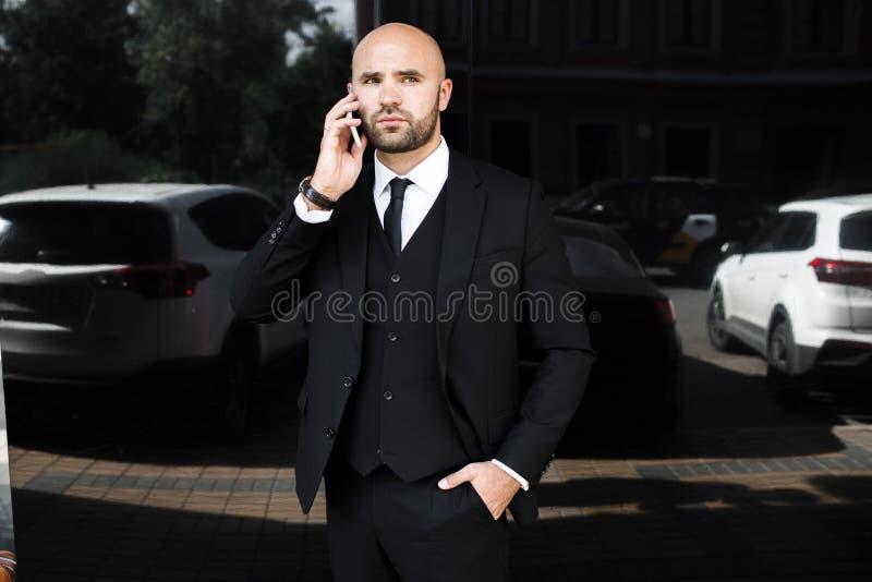 Homem de negócios perto do escritório que fala no telefone fotografia de stock