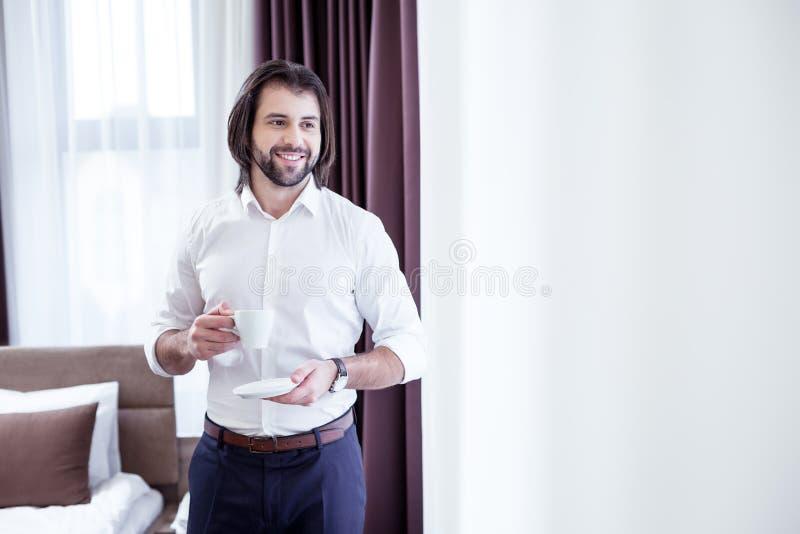 Homem de negócios positivo alegre que aprecia sua bebida da manhã imagem de stock