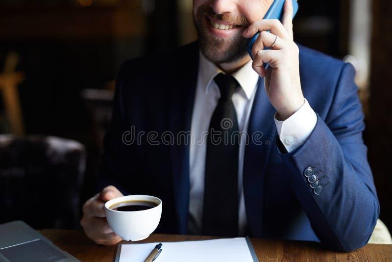 Homem de negócios positivo com café que chama o telefone fotografia de stock